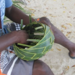 Archer making palm basket